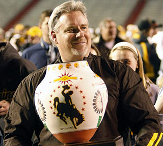 Wyoming's first-year coach Dave Christensen proudly displays the winner's trophy.  (AP)