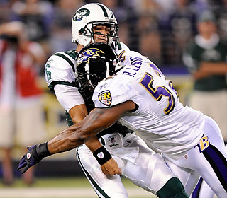 Mark Sanchez is hit by Ray Lewis and throws an interception on his first pass attempt.  (Getty Images)