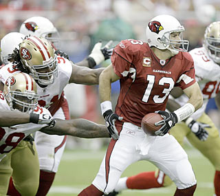 The Niners' defense applies heavy pressure as it swarms Kurt Warner early and often throughout the game.