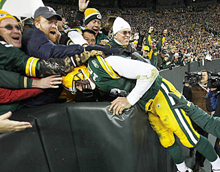 Green Bay's Aaron Rodgers takes the Lambeau Leap after his rushing touchdown in the second half.  (AP)