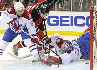 Travis Zajac, one of five scorers for New Jersey, battles in front to knock the rebound in the net. (AP)
