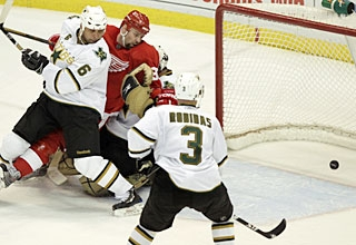 A goal by Tomas Holmstrom (center) is disallowed for incidental contact with goalie Marty Turco. (AP)