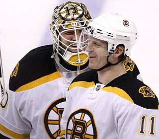 P.J. Axelsson (right) is popular with goalie Tim Thomas after his game winner. (AP)