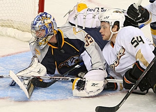 Pekka Rinne faces pucks and all comers like Bobby Ryan, who crashes the net.  (Getty Images)