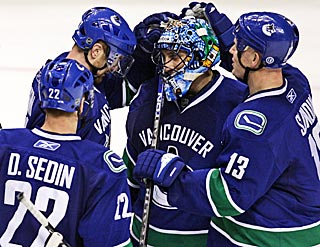 From left to right, Sedin, Sedin and Sundin give props to Roberto Luongo on his 25-save outing.  (AP)