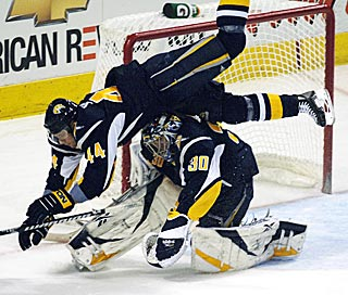 What a first period for Ryan Miller. He faces 18 shots and teammate Andrej Sekera plows him over.  (AP)