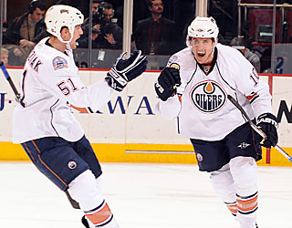 The Oilers' Shawn Horcoff (10) celebrates his third-period goal with Kyle Brodziak. (Getty Images)
