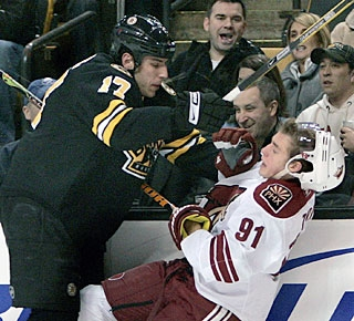 Milan Lucic takes down Kyle Turris with a nasty check as the home fans enjoy the physical part. (AP)