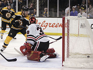 Boston's Mark Recchi (28) slips the puck past Cristobal Huet for one of his two goals on the afternoon. (AP)