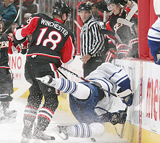 Jesse Winchester sends Nikolai Kulemin into the wall as his Senators bounce the Leafs.  (Getty Images)