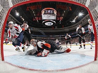 Matt Carle (25) uses a cross-check to shove Alexander Ovechkin (8) away from the crease. (Getty Images)