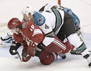 Despite being checked hard by Rob Blake from behind, Shane Doan is still able to put the puck in the net. (AP)