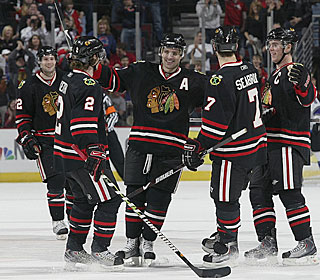 After missing 16 games because of a knee injury, Patrick Sharp (middle) nets two goals.  (Getty Images)