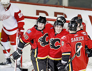 Mike Cammalleri (middle) and the Flames celebrate many goals at the expense of the Red Wings.  (AP)