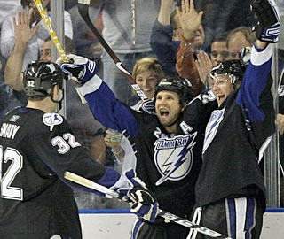 Martin St. Louis (center) is quickly approached by celebrating teammates after scoring the winner. (AP)