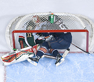 The Oilers' Ales Hemsky crashes into Niklas Backstrom in the Wild's narrow victory.  (Getty Images)