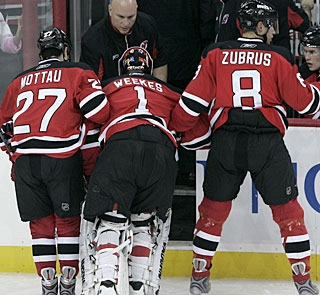 Kevin Weekes is helped off the ice after injuring his leg in the first minute of the second period. (AP)