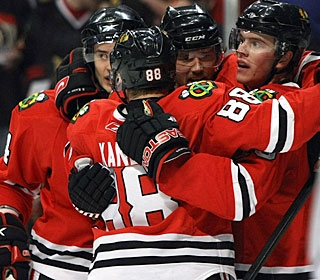 Jonathan Toews (right) and linemates celebrate his team-leading 32nd goal. (Getty Images)