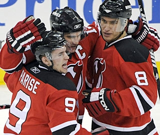 Zach Parise and Jamie Langenbrunner (center) set each other up to record a goal and assist. (AP)