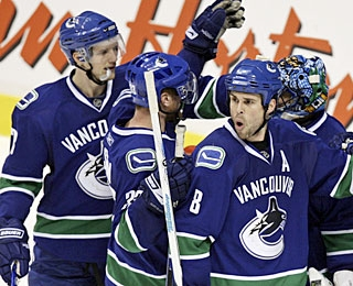 Canucks players acknowledge Roberto Luongo is a principal factor after making 25 saves. (AP)