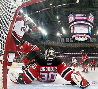 Eric Staal jumps over Martin Brodeur to celebrate Tim Gleason's winner in overtime. (Getty Images)