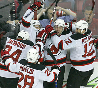 Travis Zajac (center) gets swarmed by teammates after he scores the game winner in overtime.  (AP)