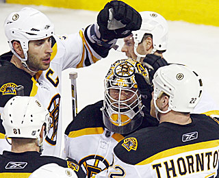 Tim Thomas (center) receives props after saving 23 shots as the Bruins move closer to the next round.  (AP)