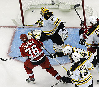 Carolina's Jussi Jokinen knocks in the winner past Boston goalie Tim Thomas in overtime. (AP)