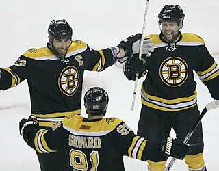 Phil Kessel (top right) celebrates one of his two goals. Marc Savard assists on both.  (AP)