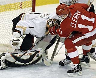 Daniel Cleary knocks the puck under goalie Jonas Hiller with three minutes to play. (AP)