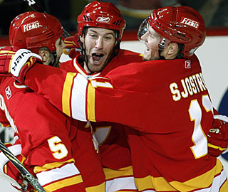 Brandon Prust (center) celebrates his first goal in the Flames uniform and second of his NHL career. (AP)