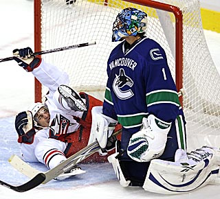 Columbus' Antoine Vermette celebrates his first-period goal while sliding into Roberto Luongo.  (AP)