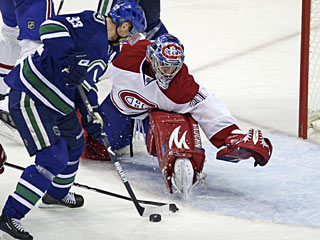 Henrik Sedin controls the puck and eludes goalie Carey Price for one of his two goals. (AP)
