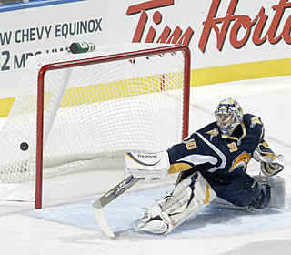 Ryan Miller stops 23 shots and on this one gets help as the puck bounces off the goal post. (Getty Images)