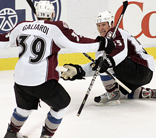 Cody McLeod (right) celebrates one of his two goals as the Avs rally past the Red Wings.  (AP)