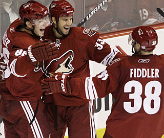 Peter Mueller, Adrian Aucoin (center) and Vernon Fiddler get the celebration started in Phoenix. (AP)