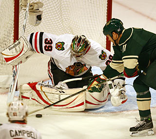 Owen Nolan tries to slap the puck past Cristobal Huet, but fails to score on the 'Hawks goalie.  (Getty Images)