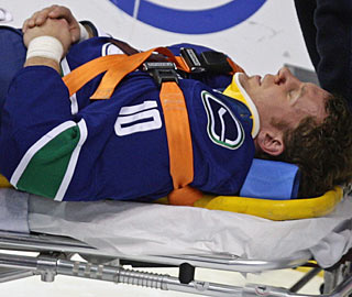 Vancouver's Ryan Johnson is taken off on a stretcher after sliding headfirst into the end boards. (AP)