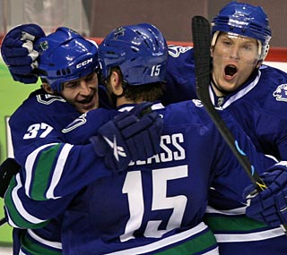 The Canucks embrace after Rick Rypien (left) nets the go-ahead score 8:48 into the third period.  (AP)