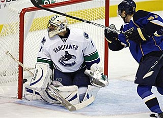 David Perron completes his hat trick in the third period by getting a shot past Roberto Luongo.  (AP)