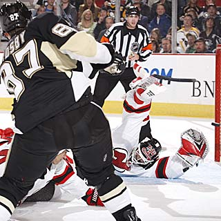Martin Brodeur sprawls out to make a tough save against Sidney Crosby. (Getty Images)