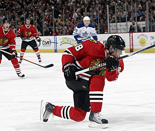 Teammates chase down Patrick Kane, who beats Vesa Toskala with this hard shot. (Getty Images)