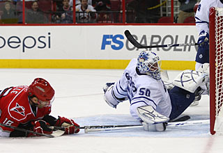Stephane Yelle reaches a loose puck to put it in the net for his first goal with Carolina. (Getty Images)