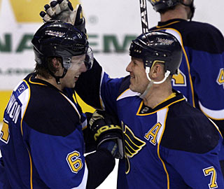 Keith Tkachuk (7) congratulates Erik Johnson for the defenseman's quick winner in the extra period. (AP)