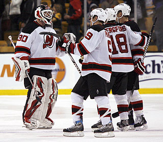 Martin Brodeur is congratulated by teammates after becoming the NHL's all-time minutes leader. (AP)