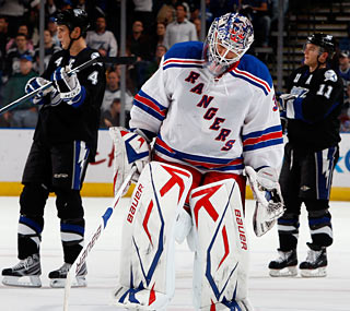 A dejected Henrik Lundqvist skates off the ice after giving up four goals in the blowout loss.  (Getty Images)