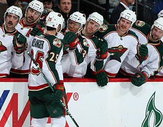 Eric Belanger gets love from the Wild bench after he scores the team's first goal. (Getty Images)