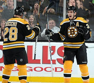 Patrice Bergeron (right) celebrates his goal with Mark Recchi, who tallies three assists.  (Getty Images)