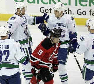 The victorious Canucks surround New Jersey's Zach Parise after a goal in the first period.  (AP)