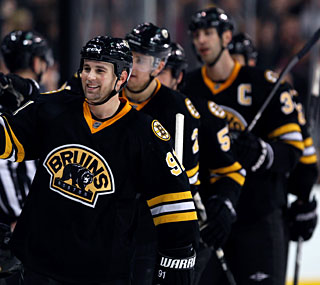 Marc Savard (front) continues to light it up, earning the first hat trick of the season for Boston.  (AP)
